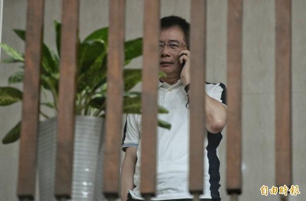 今晚11點半,蔡妻仍在庭訊中,蔡正元原本面露憔悴,坐在2樓偵查庭外等候開庭,突然起身講電話。(記者林正堃攝)