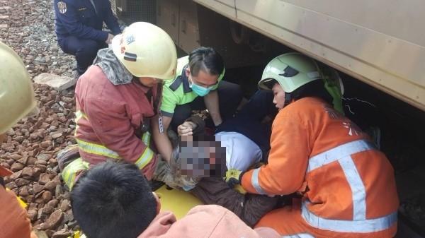 警方與消防人員將月台跳下的董姓退役軍官從列車底下拉出。(記者蔡彰盛翻攝)