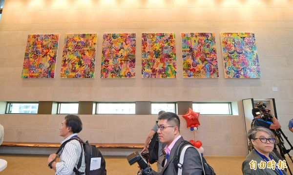 "Reporters visiting the new American Institute in Taiwan compound in Taipei's Neihu District yesterday walk beneath a set of paintings on the theme of ""impressions of Taiwan"" by US painter Ryan McGinness.