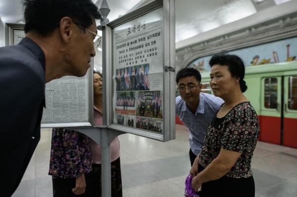 北韓民眾今在平壤地鐵站,閱讀北韓勞動黨機關報《勞動新聞》針對川金會的相關報導。(法新社)
