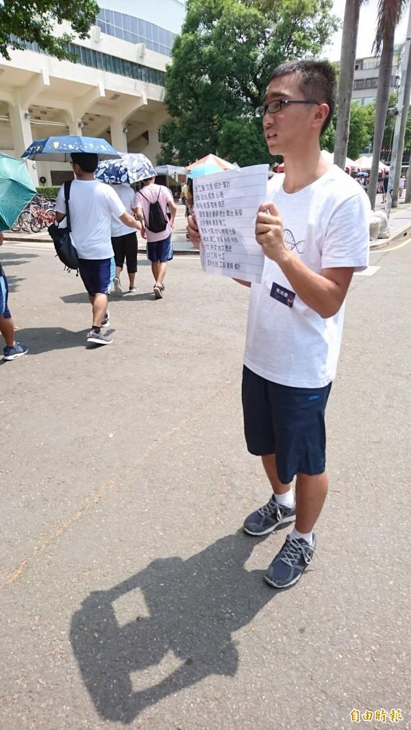 馬姓學生志工不畏陽光酷熱,立在中央站好幾個小時舉牌導引。(記者洪瑞琴攝)