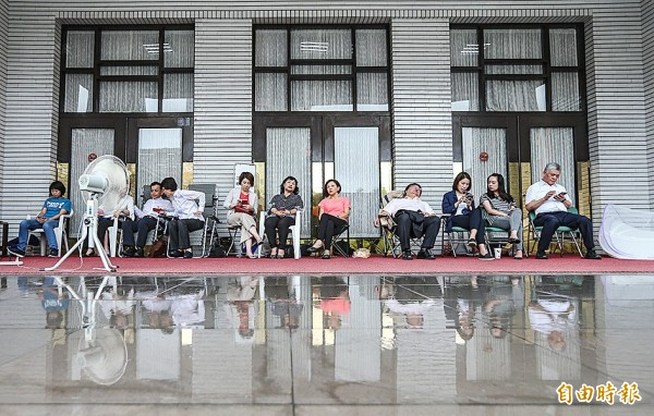 Legislators wait outside the entrance to the legislative chamber before attending an extordinary session at the Legislative Yuan in Taipei yesterday.