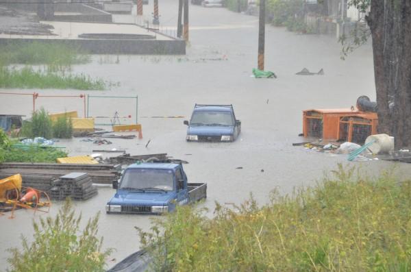 三爺溪暴漲,沿岸氾濫成災,來不及開出去的車輛,都泡在水中。(記者吳俊鋒攝)