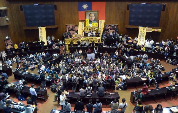 反服貿學生團體昨日晚間衝進立法院並占據議場,警方今日發動攻堅,但無法突破障礙,大批學生坐在議場中間集結。(記者王藝菘攝)