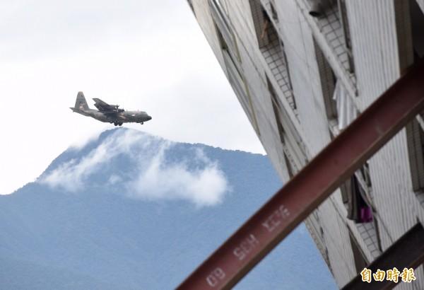 載運人道救援物資的新加坡軍方C-130運輸機9日下午降落花蓮機場,落地前正好飛過傾倒的雲翠大樓後方。(記者羅沛德攝)