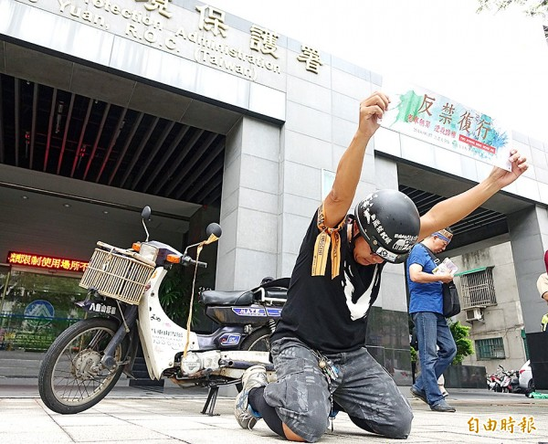 An owner of a two-stroke scooter yesterday protests outside the Environmental Protection Administration's offices in Taipei against the administration's plan to tighten emissions standards for old vehicles. Photo: Liu Hsin-de, Taipei Times