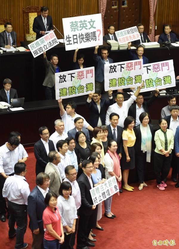 國體法三讀通過後,藍綠立委在議場中高舉標語。(記者劉信德攝)