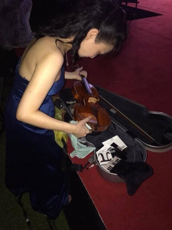 國慶音樂會首席演奏家馮楚軒心疼的擦拭被雨淋濕的小提琴。(圖由馮楚軒提供)
