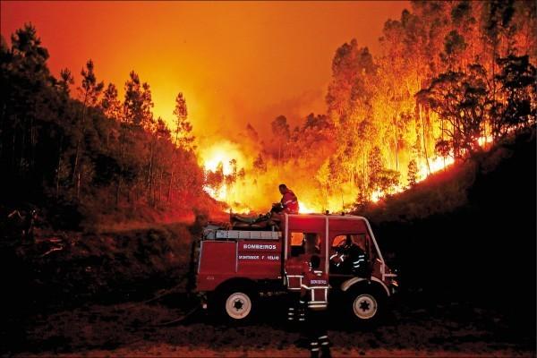 葡國中部大貝德羅高鎮17日爆發森林大火,消防員挺進火場救災,造成至少62人喪生、60人受傷。(路透)