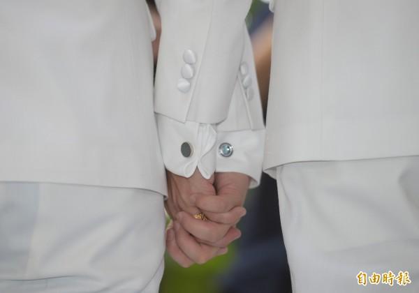 同志情侶蔡意欽(右)與佑佑(左)8日在親友的祝福下完成終生大事,兩人十指緊扣。(記者張嘉明攝)