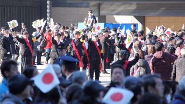 日本明仁天皇慶祝84歲壽誕,突出現民眾手持「台灣民政府」旗幟湧入現場。(圖翻攝自環球網)