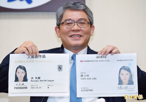 Deputy Minister of the Interior Hua Ching-chun holds enlarged images of the most popular (left) and winning national identification card designs at a news conference in Taipei yesterday. Photo: Liao Chen-huei, Taipei Times