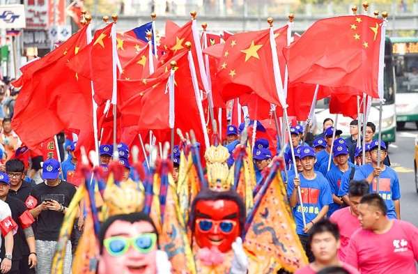 Members of the China Unification Promotion Party commemorate China's national day by waving and wearing China's national flag near Taipei Railway Station on Oct. 1 last year. Photo: Peter Lo, Taipei Times