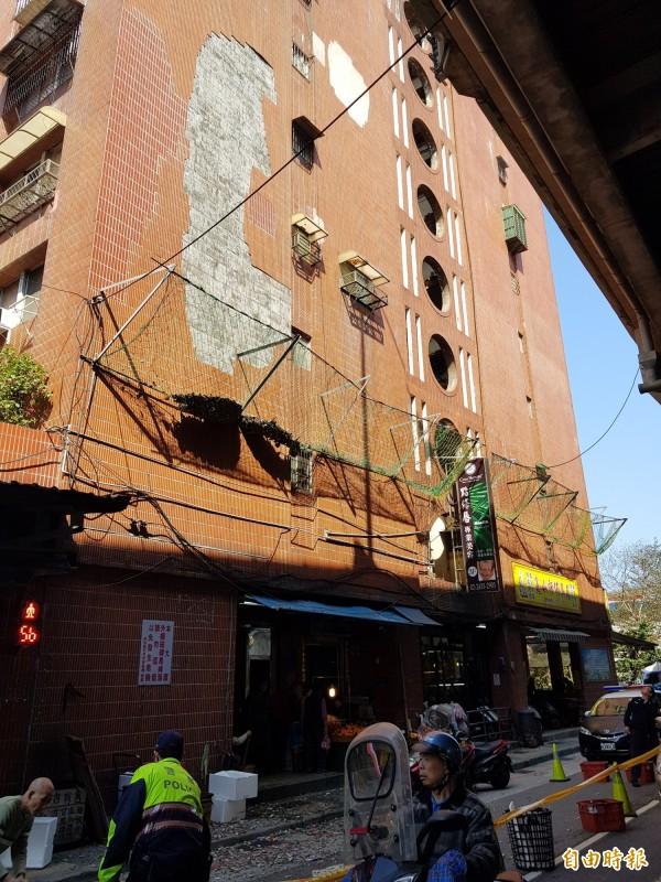 基隆市華三街成功國宅外牆磁磚脫落,里長到場提醒行人快速通過。(記者俞肇福攝)