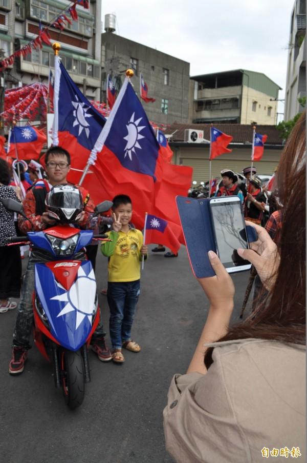 劉威誠(左一)將機車改為國旗塗裝,吸引小朋友合影留念。(記者周敏鴻攝)