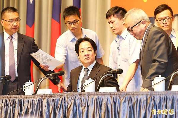 Premier William Lai, center, attends a news conference at the Executive Yuan yesterday at which he announced details of a Cabinet reshuffle that sees Executive Yuan spokesman Hsu Kuo-yung, left, take over as minister of the interior, among other appointments. Photo: CNA
