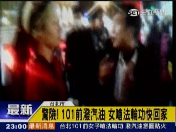 身穿紅衣的女子晚間在101大樓廣場前,向法輪功成員嗆聲「快滾回家」,之後還把寶特瓶內的汽油潑灑在地上,試圖點火。(圖片擷取自《三立新聞》)