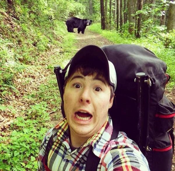 一名男性遊客假裝驚恐、搞笑與野熊自拍。(圖取自東網)