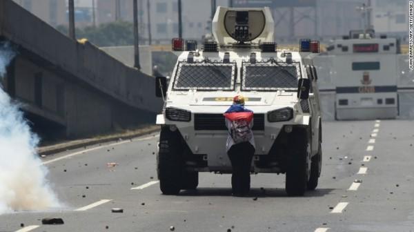 委內瑞拉一名婦女參與反政府獨裁抗爭,她孤身擋在裝甲車前。(法新社)
