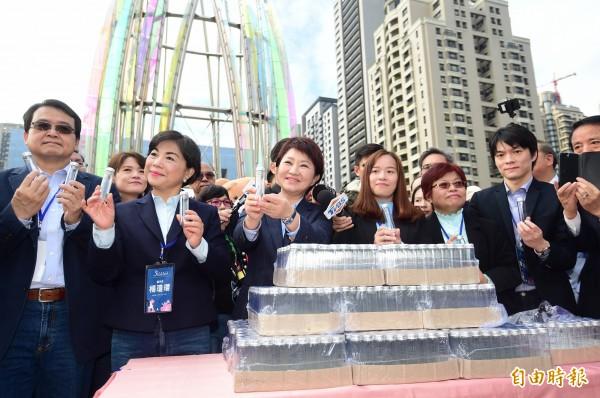 新任台中市長盧秀燕送觀禮市民一人一瓶谷關的空氣,象徵新市政府的決心。(記者廖耀東攝)