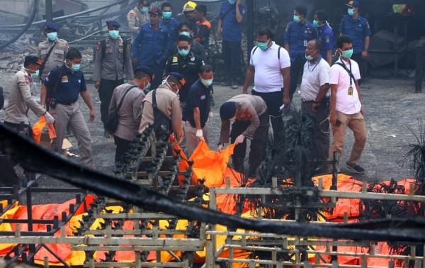 爆炸現場滿目瘡痍,印尼警方拖出一具又一具罹難者遺體。(路透)