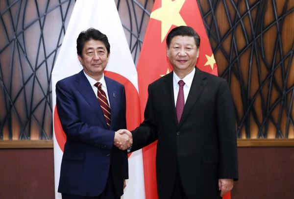 日本首相安倍(左)被疑幫中國國家主席習近平(右)傳話。(美聯社)