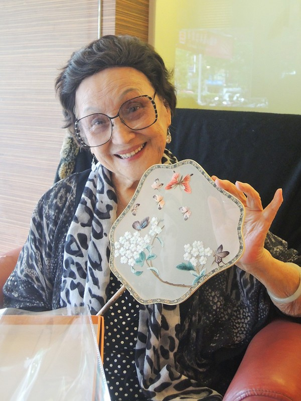 Dai Yu-mei, a member of the Saisiyat Aborigine community from Hsinchu County's Wufeng Township, holds a fan with an embroidered flower and butterfly design on Jan. 26 in the county. Photo: Liao Hsueh-ju, Taipei Times