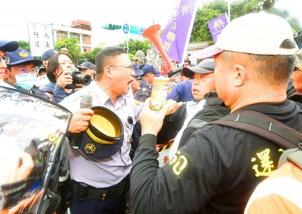 A police officer argues with pension reform protesters yesterday on Ketagalan Boulevard near the Presidential Office Building in Taipei. Photo: Fang Pin-chao, Taipei Times