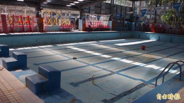 三民公園泳池底板多處掀起、裂開,無法使用。(記者蔡亞樺攝)