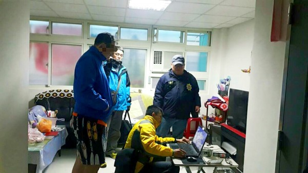 Police examine the computer of a man, surnamed Ho, left, in New Taipei City on Monday. Ho was arrested for allegedly sharing a massive amount of child pornography online. Photo: Huang Liang-chieh, Taipei Times