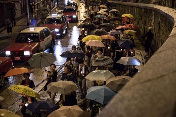 香港支聯會在週六晚間進行哀悼劉曉波的燭光遊行,一開始有數百人從中環遮打花園出發,並一路遊行到西環中聯辦門外。(法新社)