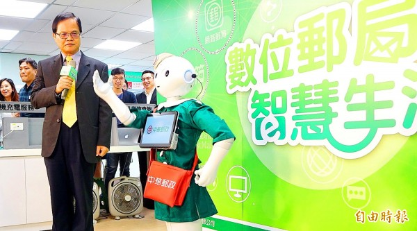 Chunghwa Post vice president Wu Yuan-jen interacts with a Pepper robot at the Jinnan Post Office on Taipei's Aiguo E Road yesterday.