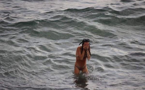 該名孕婦生產完後,用海水抹去臉上的汗水,彷彿剛從海中游完泳似的走上沙灘。(圖擷取自每日郵報)