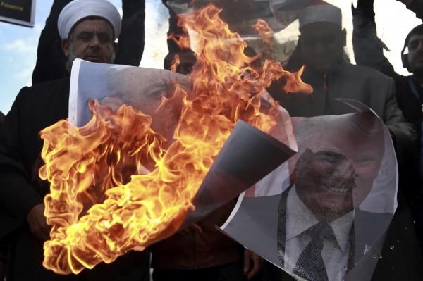 巴勒斯坦人民焚燒美國總統川普與以色列總理尼坦雅胡的頭像,來表達強烈不滿。(美聯社)