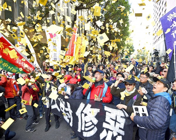Representatives of several labor groups yesterday throw joss paper at the Legislative Yuan after the legislature passed the third reading of the amendments to the Labor Standards Act. Photo: Chen Chih-chu, Taipei Times
