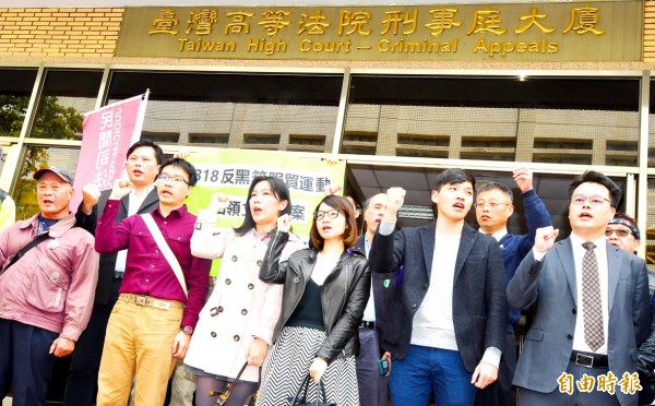 People who were indicted in connection with the Sunflower movement's 2014 occupation of the Legislative Yuan raise their fists outside the Taiwan High Court yesterday after the court upheld their acquittal.