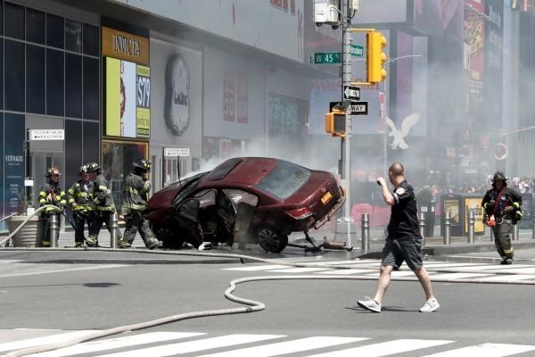 肇事車輛卡在百老匯45街交叉口的防撞柱上,消防人員在一旁灑水警戒。(路透)
