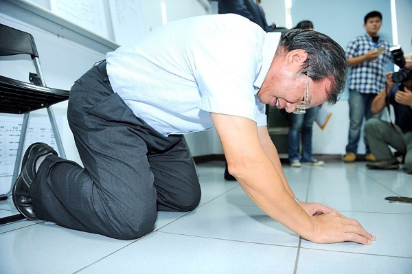 Chang Guann Co chairman Yeh Wen-hsiang kneels in Kaohsiung on Sept. 11, 2014, to apologize for a tainted oil scandal. Photo: Chang Chung-yi, Taipei Times