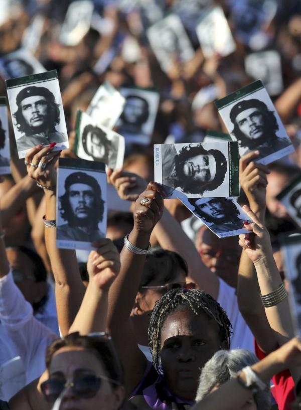 古巴人民手握切格拉瓦相片,視其為革命英雄。(歐新社)