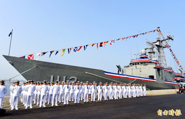 Sailors stand next to one of two Perry-class guided missile frigates, which were commissioned yesterday in a ceremony at the Zuoying naval base in Kaohsiung's Zuoying District. Photo: Chien Jung-fong, Taipei Times