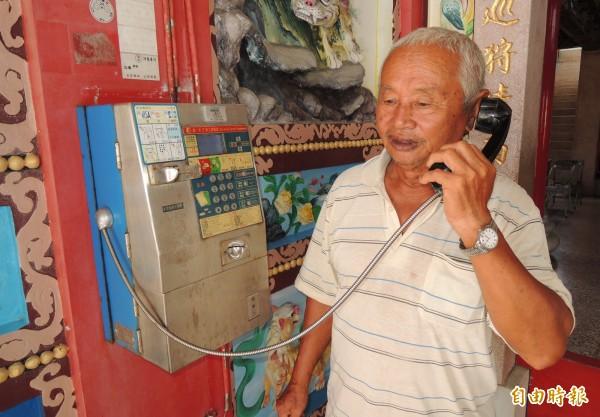 王州成視井仔腳庄內僅存一支公用電話為寶貝,三不五時就投幣用一用,以免它被拆。(記者楊金城攝)