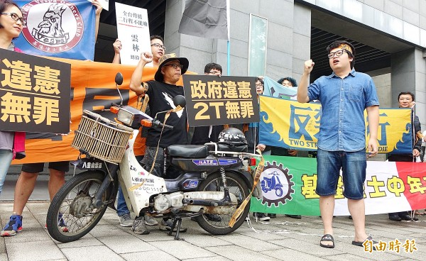 Owners of two-stroke scooters yesterday hold placards at a protest outside the Environmental Protection Administration's offices in Taipei against the administration's plan to tighten emissions standards for old vehicles. Photo: Liu Hsin-de, Taipei Times