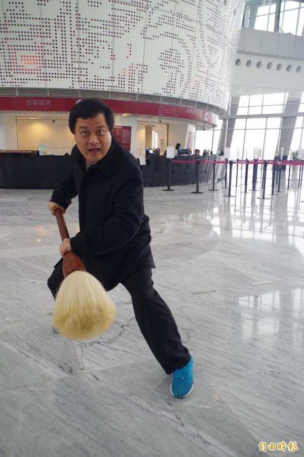 陳世憲用高約120公分的毛筆,替故宮南院寫巨幅春聯,寫之前還要先暖身。(記者王善嬿攝)