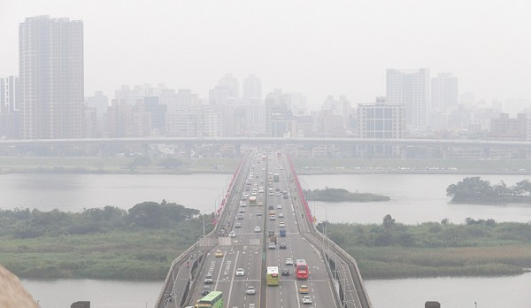 New Taipei City is shrouded in smog in a picture taken from Taipei across the Zhongxiao Bridge yesterday. Photo: CNA