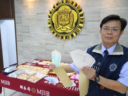 調查局北機站副主任陳彥有展示所查獲的空頭支票。(記者謝君臨翻攝)