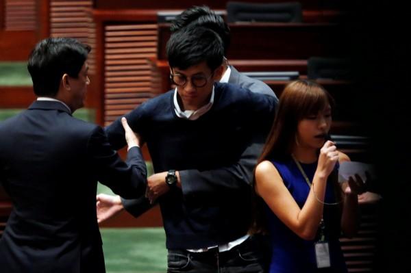 梁頌恆、游蕙禎在嘗試進入議會時被保安組成的人牆阻擋,雙方發生推擠衝突,過程中,兩人用自備的擴音器自行宣誓。(路透)