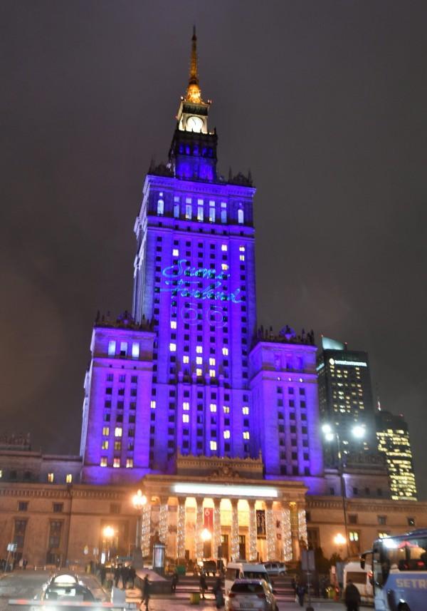 波蘭首都華沙的科學文化宮,整棟藍光搭配慶祝100周年的字樣。(歐新社)