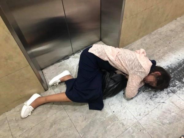 1名身穿皮膚色罩衫、深藍色長裙的女子,臥倒在電梯大樓住宅的電梯門口,身體自然彎曲且臉部倚靠在手背上酣然入睡。(圖擷取自爆料公社)