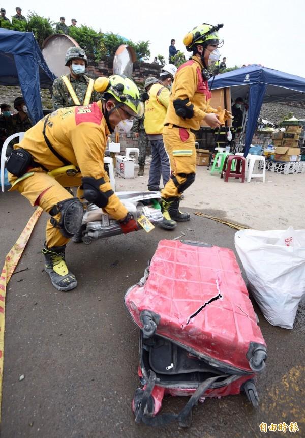怪手嘗試開挖花蓮雲翠大樓漂亮生活旅店,搜救人員9日下午於201到203號房挖出兩箱行李。(記者羅沛德攝)