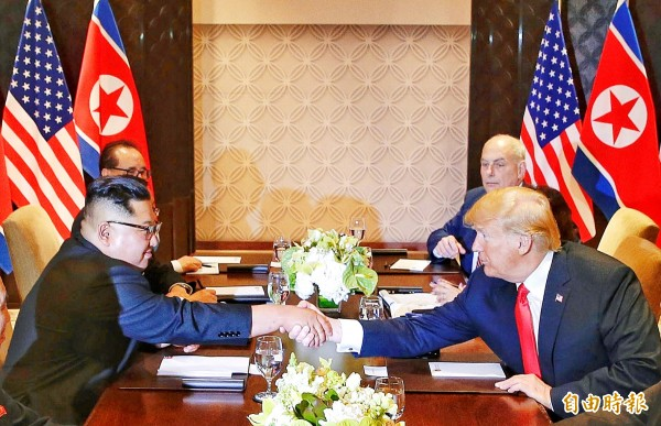 North Korean leader Kim Jong-un, left, and US President Donald Trump shake hands at the Capella resort on Sentosa island in Singapore yesterday as White House chief of staff John Kelly, back right, looks on.
